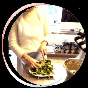 Vignette ronde d'une femme dressant une assiette dans une cuisine professionnelle