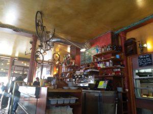 Photo du comptoir d'un café restaurant avec un vélo au plafond